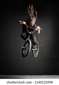 Young man with dreadlocks jumping on his BMX bike. Extreme sports.