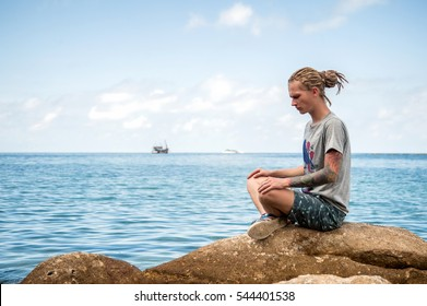 Young man with dreadlocks meditating at the beach