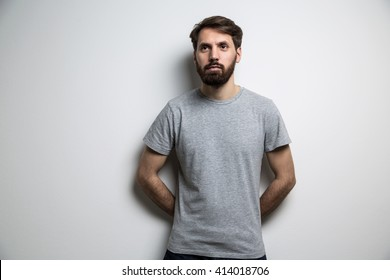 Young man dressed in blank grey shirt on light background. Mock up