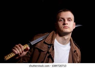 Young man dressed in a brown coat and white t-shiert, holding a katana.Modern samuria.Fashion portrait.Urban warior.Dramatic light