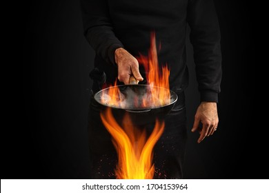 Young man dressed in jumper and jeans. He is holding burning wok pan with smoke above fire, against black studio background. Cooking concept. Close up