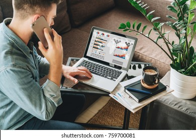 Young man, dressed in shirt, sits at home on couch at coffee table,uses laptop with graphs, charts, diagrams on screen, talks on his cell phone,calling. Online marketing,education, e-learning.Startup.