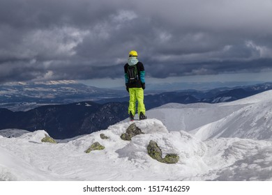 Young man dressed in winter clothes stands on stone covered with snow and enjoys view on High tatras in Slovakia. Concept of determination, self-sacrifice and hard working.