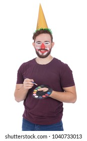 A young man drew a clown on his face holding a color palette and wearing a cone, isolated on a white background.