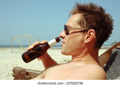 Young man drinking beer on the beach
