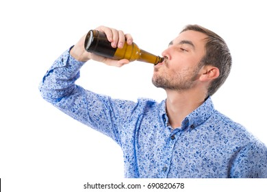 Young man drinking a bottle of beer isolated on white background