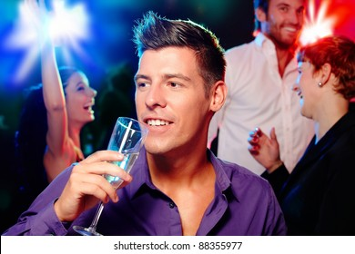 Young man drinking champagne at a party, people dancing at background.?