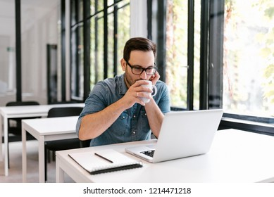 Young man drinking coffee ar tea while working in modern office.
