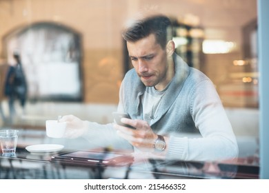 Young man drinking coffee in cafe and using phone