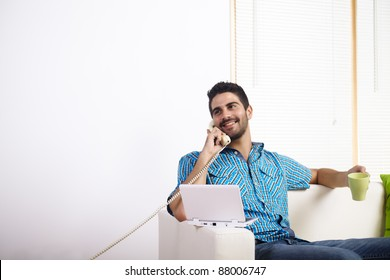 Young man drinking coffee and using laptop while talking on phone.