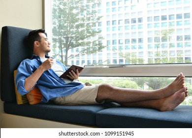 Young man drinking coffee while sitting on sofa at home with the book in his hand