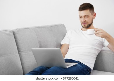 Young man drinking coffee while working with laptop at home
