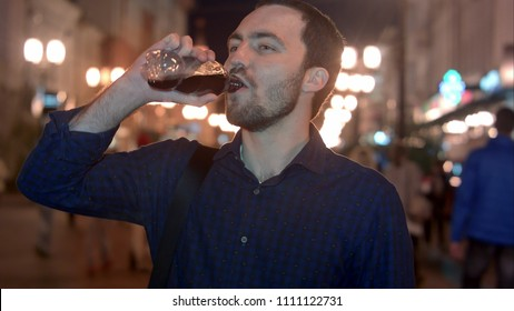 Young man drinking coke at night city