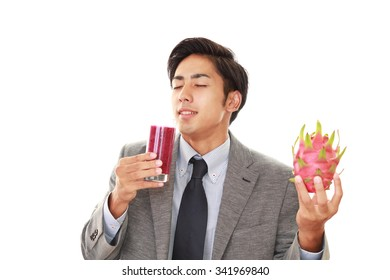 The young man drinking a glass of juice