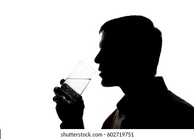 Young man drinking a glass of sparkling water - silhouette