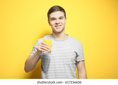 Young man drinking juice on color background