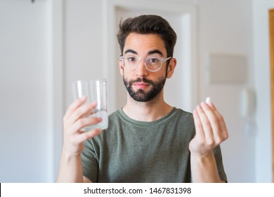 Young man drinking medicine at home
