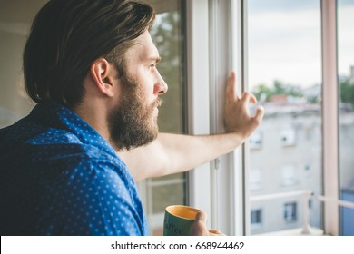 Young man drinking morning coffee by the window
