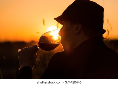 A young man drinking red wine at sunset