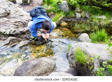 Young man drinking water from a spring. Hiking trail and alpine landscape of the Preikestolen and Lysefjord area in Rogaland, Norway