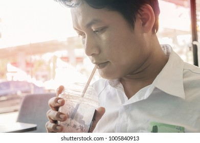 young man drinking water through use straws