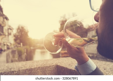 Young man drinking wine outdoors.
