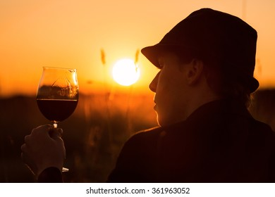 A young man drinking wine in the sundown