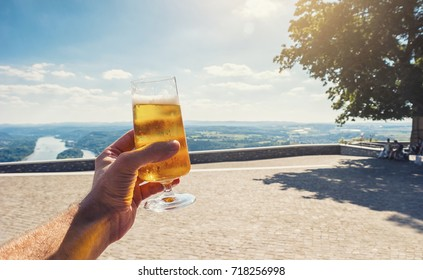 young man drinks fresh beer in a beer garden at summer
