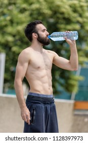 Young man drinks water after practice, shirtless