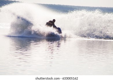 young man drive on the jet ski above the water at sunset .silhouette. spray.