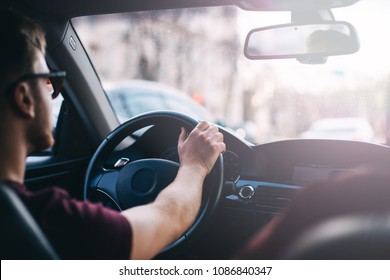 young man driving a business car. trip of a businessman in sunny weather.