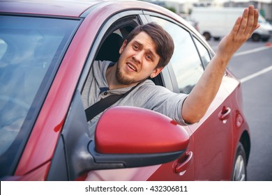 The young man driving the car angry, stuck in a traffic jam