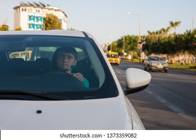 Young man driving a car in the city. Portrait of a guy in a car. Travel and vacations concepts. Handsome elegant serious man drives a car in the street