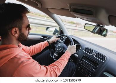 Young man driving a car, interior shot
