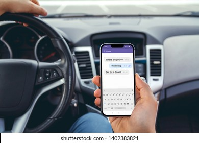Young man driving a car with a phone in his hand. Don't text and drive