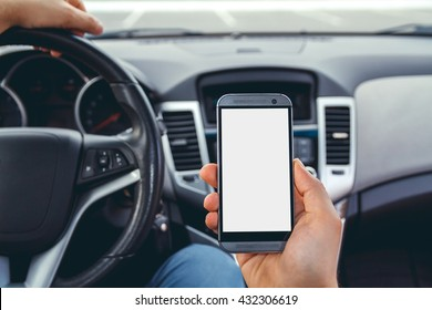 Young man driving a car with a phone in his hand. Multitasking. Don't text and drive