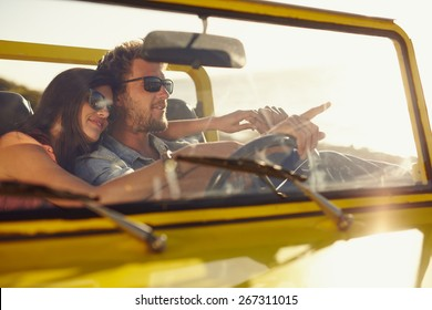 Young man driving car pointing something interesting to his girlfriend. Caucasian couple on summer holiday, Romantic couple on road trip.