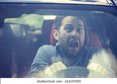 Young man driving a car shocked about to have traffic accident, windshield view
