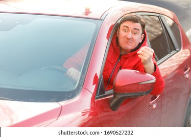 A young man driving a car swears in traffic emotionally gesturing