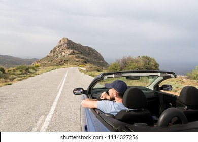Young man driving in convertible blue car without roof on mountain road in Naxos island, Greece. Wide angle lens shot.
