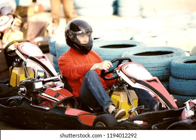 Young man is driving go-kart car with speed in a playground racing track - go kart is a popular leisure motor sports.