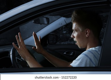 Young man driving in his car at night