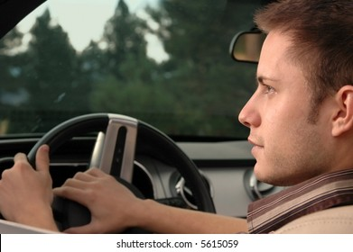 A young man driving his car into the late afternoon sun