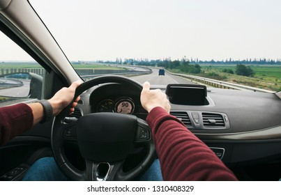 The young man driving the modern car on asphalt road