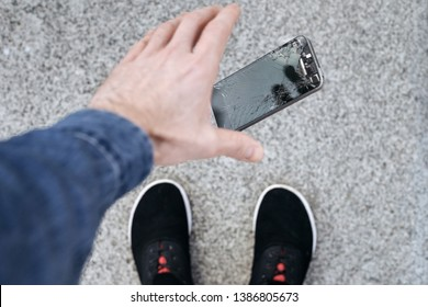 Young man dropped his smarphone. Falling of broken smarphone with cracked screen glass.
