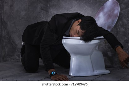 Young man drunk or sick vomiting on toilet bowl