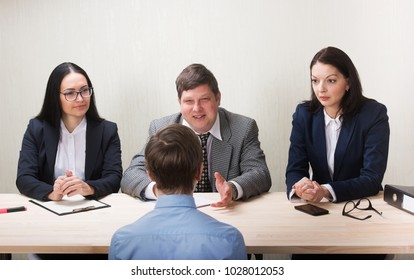 Young man during job interview and members of managemen