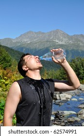 The young man eagerly drinking water from plastic bottles, white mountain river, mountain top