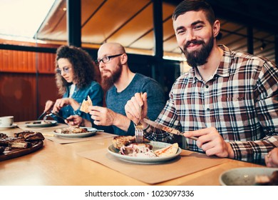 Young man eat meat and rest with friends in cafe.