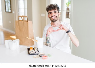 Young man eating asian sushi from home delivery smiling in love showing heart symbol and shape with hands. Romantic concept.